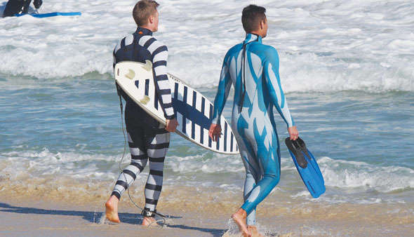Surfers wearing anti shark wetsuits