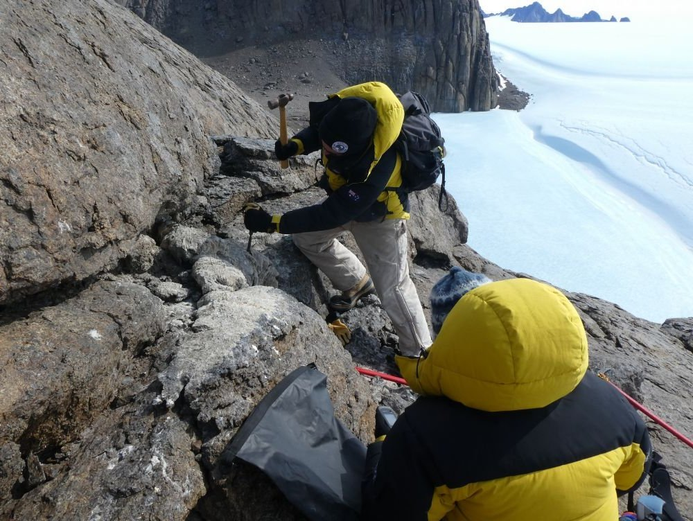 Marcus Salton chisels a thick sample of very hard mumijo off rocks outside a nest cavity in the Masson Range near Mawson research station. Photo: Marcus Salton