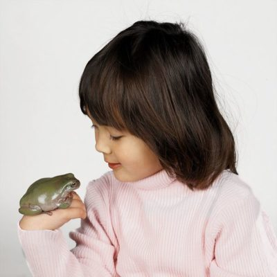 Girl with green tree frog